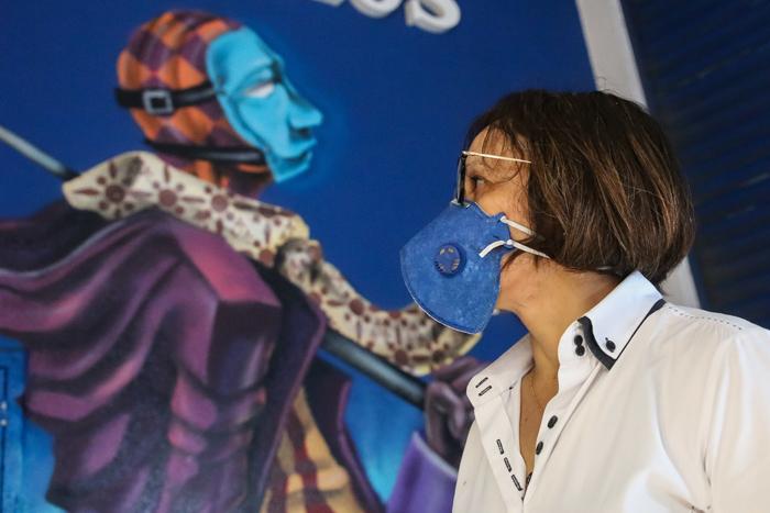 Pedestres passando em frente a grafites que sugerem uso de máscaras devido ao novo coronavírus