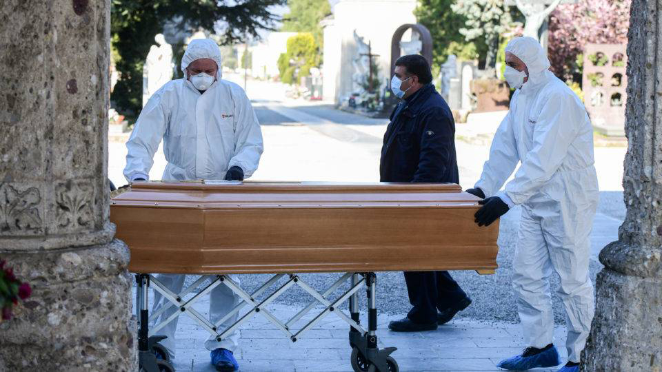 Pessoas com equipamentos de proteção descarregam um caixão de um carro funerário no cemitério Monumental de Bérgamo, Lombardia