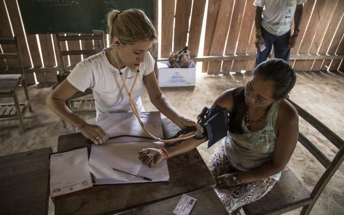 Enfermeira usa um esfigmomanômetro para medir pressão arterial da índia Kaxinawá, ação de saúde em sua aldeia