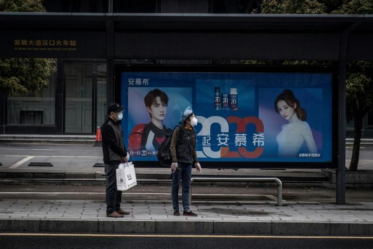Moradores esperam em ponto de ônibus em Wuhan, na província central de Hubei, na China, em 25 de março de 2020