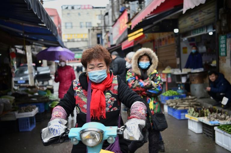 Pessoas com máscara de proteção em Wuhan, berço do coronavírus na China