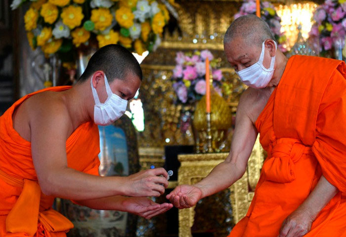 Monges budistas, usando máscaras protetoras devido ao surto de coronavírus, usam álcool em gel enquanto participam de uma cerimônia em Wat Suthat Thepwararam em Bangkok, Tailândia