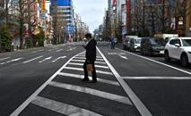 Homem com máscara cruza uma rua no bairro de Akihabara, em Tóquio, 30 de março de 2020 (AFP)
