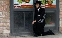 Policial israelense detém um judeu ultraortodoxo durante patrulha em Jerusalém (AFP)