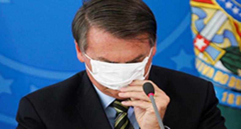 Presidente Jair Bolsonaro, o timoneiro na travessia da pandemia, com sua inabilidade em colocar uma máscara durante coletiva (Adriano Machado/ Reuters)