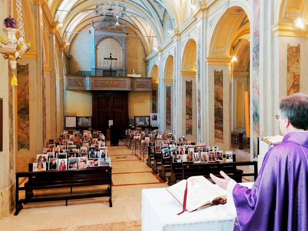 Pe. Giuseppe Corbari celebra missa sozinho diante de fotos dos seus paroquianos em Robbiano, na Itália
