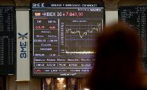 Mulher olha para tela mostrando o índice IBEX 35 na principal bolsa de valores da Espanha, em Madri, em 9 de março de 2020 (AFP)