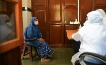 Médicos consultam mulher em centro de saúde municipal antes de teste de coronavírus  em Mumbai, em 7 de abril de 2020 (AFP)