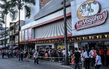 Pessoas esperam a sua vez de entrar no supermercado enquanto tomam medidas de proteção contra a propagação do novo coronavírus em Medellín, Colômbia (AFP)