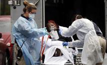 Equipe médica coloca paciente com Covid-19 em ambulância em Nova York (Stefan Jeremiah/Reuters)