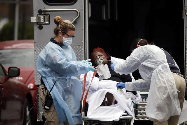 Equipe médica coloca paciente com Covid-19 em ambulância em Nova York