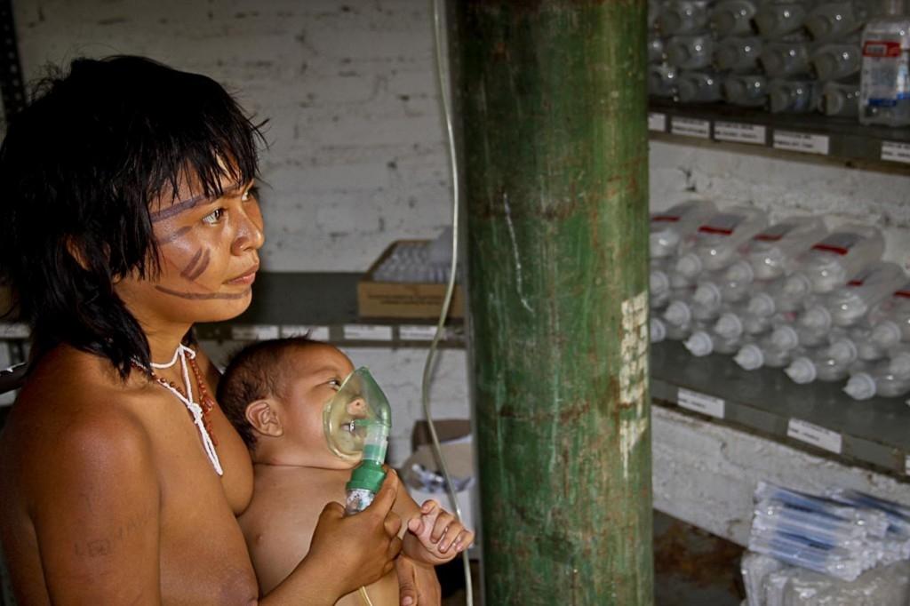 No colo da mãe, criança yanomami com problema pulmonar por causa das queimadas