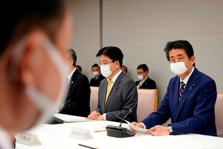 O primeiro-ministro japonês Shinzo Abe (D) declarou estado de emergência por um mês