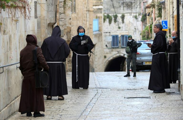 Frades fransiscanos, alguns com máscara de proteção, rezam na primeira estação da Via Crucis para marcar a Sexta-feira Santa em Jerusalém, em 10 de abril de 2020
