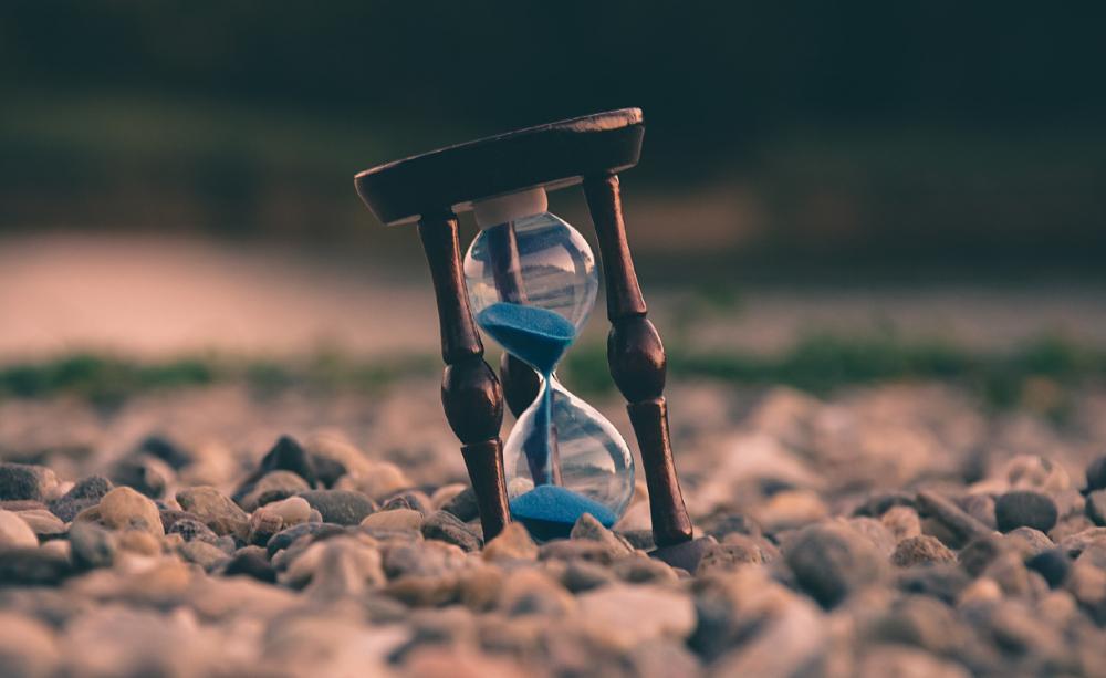 Cai vagarosamente a areia na ampulheta imaginária de apontamento de tempo 'infinito', imprevisível duradouro intervalo interveniente de horas, dias, meses a fio em calendário indefinido