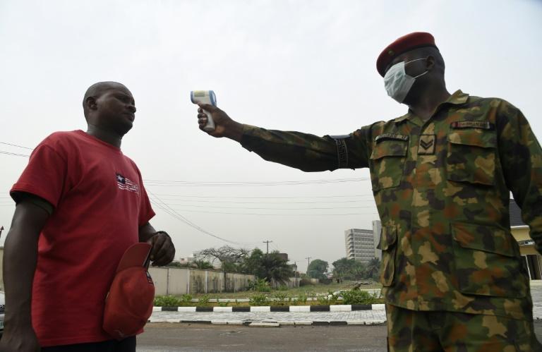Soldado verifica a temperatura corporal de um visitante do Hospital de Referência do Exército em Yaba, Lagos, em fevereiro