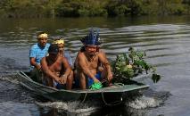 O líder indígena sateré mawé Andre Satere e outros membros do grupo retornam à comunidade de Wakiru, em Taruma, área rural a oeste de Manaus, em 17 de maio de 2020 (AFP)