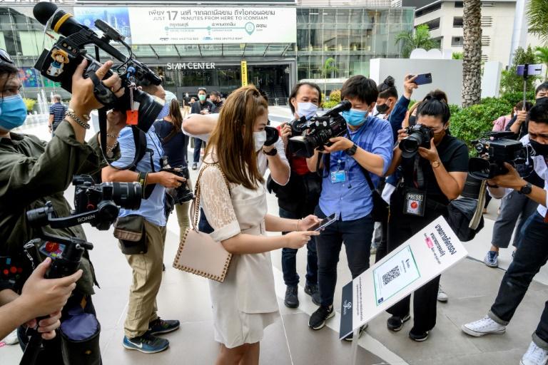 Jornalistas filmam uma mulher usando um aplicativo especial para se registrar para entrar em um shopping center, reaberto após a suspensão das medidas restritivas para conter a COVID-19, em Bangcoc, Tailândia, 17 de maio de 2020