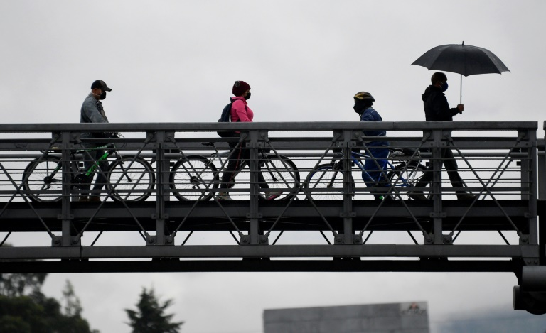 Pessoas atravessam de bicicleta uma ponte para pedestres em Bogotá