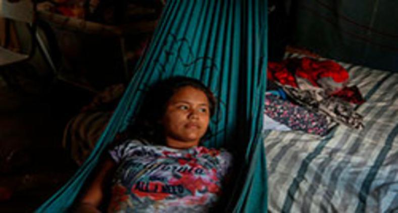 Deniane Tavares Batista, de 16 anos, descansa em rede após ser tratada com ervas medicinais após sintomas da Covid-19, na comunidade Wakiru (AFP/ Ricardo Oliveira)