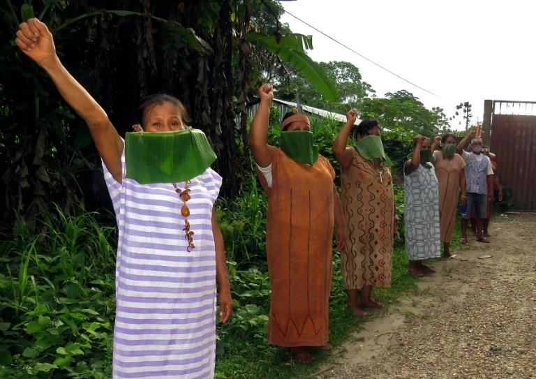Foto divulgada por membros da Federação Nativa do Rio Madre de Dios (FENEMAD) mostra indígenas das etnias Shipibo e Ese'Ejja com máscaras feitas de folhas erguendo o punho para protestar contra a falta de apoio do governo na pandemia do novo coronavírus em Madre de Dios, Peru, sul da bacia amazônica, 13 de abril de 2020