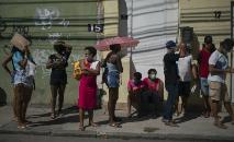 Pessoas fazem fila nas proximidades de agência da Caixa Econômica Federal no Rio de Janeiro para receber ajuda do governo durante a pandemia do novo coronavírus, em 29 de abril de 2020  (AFP)