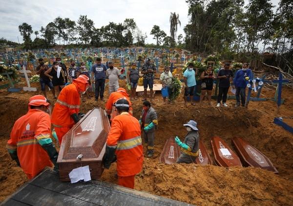 Coveiros colocam caixões de vítimas do novo coronavírus em vala comum no cemitério Parque Taruma, em Manaus