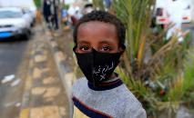 Garoto iemenita com máscara de proteção em uma rua de Sanaa, em 21 de maio de 2020 (AFP)