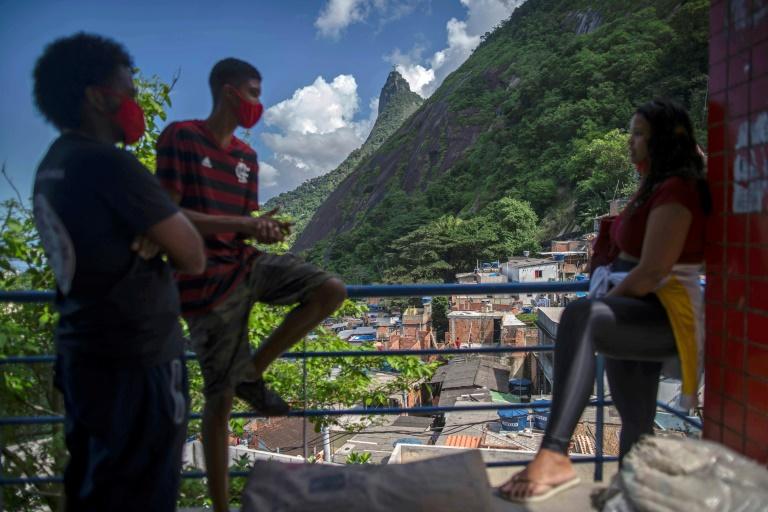 Jovens participam no dia 20 de abril de 2020 de desinfecção em favela do Rio de Janeiro