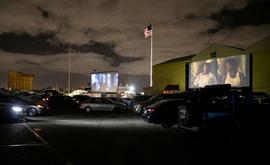 No cinema drive-in, os clientes controlam a interação social e qualquer contato com outra pessoa acontece ao ar livre (Reuters)