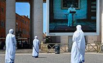 Missionárias na Caridade acompanham o Regina Coeli pelo telão instalado na Praça São Pedro (AFP)