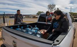 A família Larson busca a água em sua caminhonete cheia de galões, em Thoreau, Novo México (AFP)