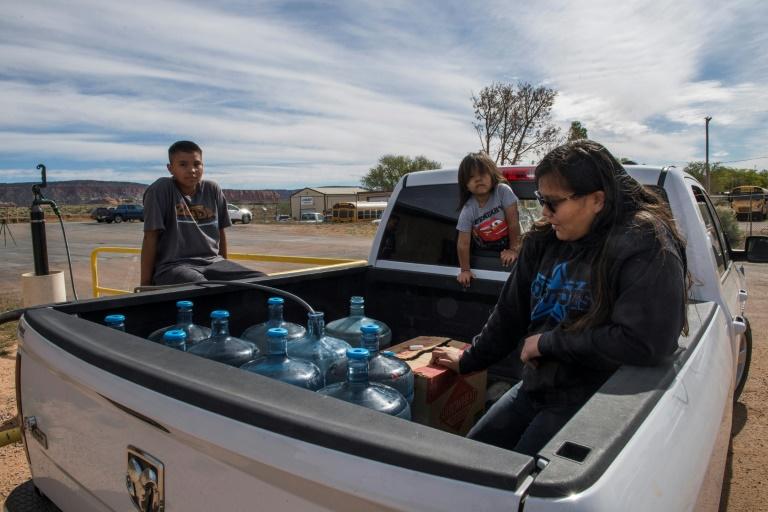 A família Larson busca a água em sua caminhonete cheia de galões, em Thoreau, Novo México