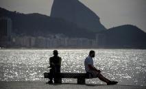 Homem usa uma máscara ao lado da estátua de Carlos Drummond de Andrade, em Copacabana (AFP)