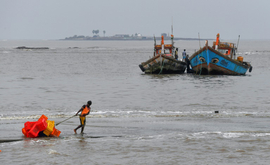 Pescador puxa caixas antes de uma tempestade ciclônica que pode atingir a costa norte de Maharashtra e Gujarat, na vila de pescadores Madh, na costa noroeste de Bombai, em 2 de junho de 2020 (AFP)