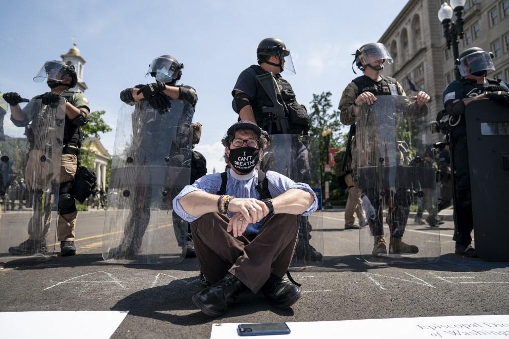 Um presbítero da Igreja Episcopal senta-se em protesto na frente da polícia enquanto bloqueiam a 16th Street perto de Lafayette Park e a Casa Branca em 3 de junho de 2020 em Washington, DC