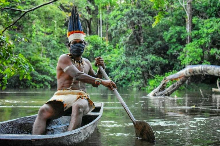 Indígena da etnia Huitoto usa máscara para evitar o contágio por COVID-19, enquanto navega com sua canoa no rio Takana, em Letícia, departamento (estado) do Amazonas, Colômbia, em 20 de maio de 2020