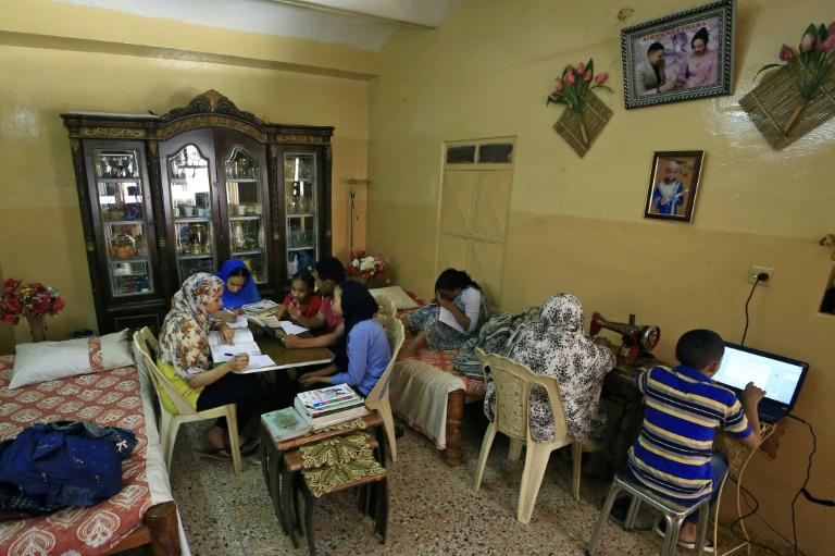Membros de uma família estudam juntos em sua casa de Cartum, após o fechamento de escolas e universidades pelo coronavírus em março