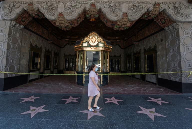 Mulher passa na frente do famoso El Capitan Theatre, em Hollwood, Los Angeles, fechado por causa da pandemia do novo coronavírus