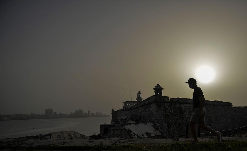Homem caminha perto do Castelo de Morro enquanto nuvem de poeira do Saara encobre a cidade de Havana, em Cuba, na quarta-feira (24)