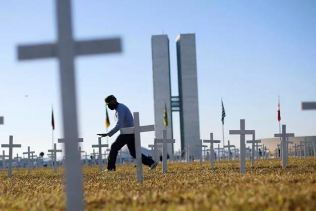 Manifestantes carregavam cruzes em protesto às mortes pela Covid-19