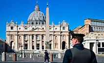 Policial de máscara, em frente à Basílica de São Pedro de Roma, em 11 de maio de 2020 (AFP)