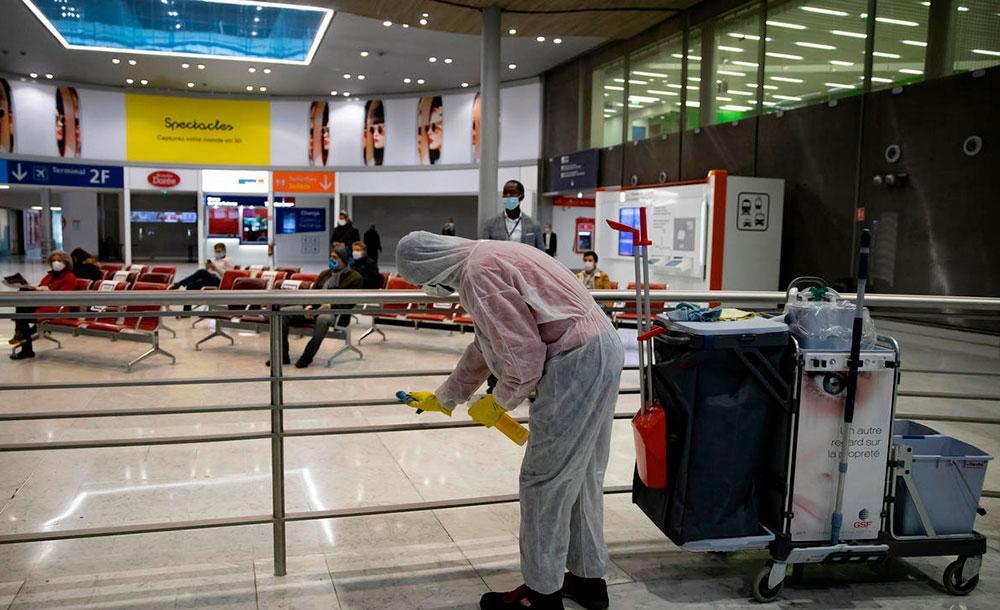 Funcionário limpa corrimão do Aeroporto Charles de Gaulle, em Paris