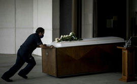 Funcionário empurra um caixão para o crematório em Nova York (Arquivos/AFP)