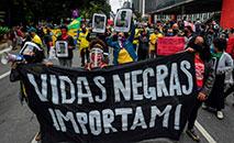 Manifestantes seguram faixa que diz 'Vidas negras importam!' contra o racismo e contra o presidente Jair Bolsonaro, em São Paulo no dia 14 de junho (AFP)