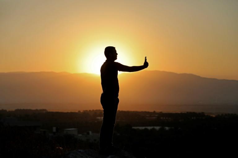 Um palestino tira uma selfie ao nascer do sol na cidade de Marj Al Ghazal, no vale do Jordão, em 1º de julho de 2020