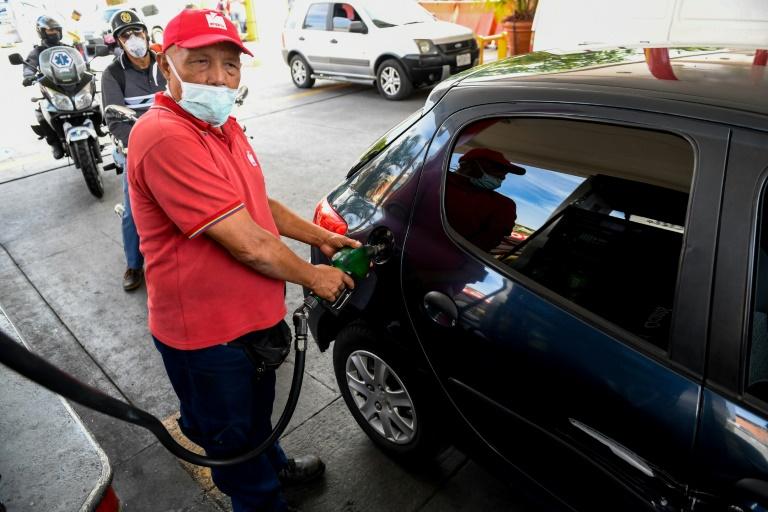 Funcionário de posto de gasolina abastece carro em Caracas