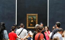 Grupo de visitantes contempla a 'Mona Lisa' no Museu do Louvre em 6 de julho de 2020 (AFP)