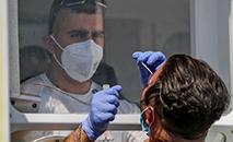Profissional de saúde aplica teste para verificar a presença do novo coronavírus no paciente (Ahmad Gharabli/AFP)