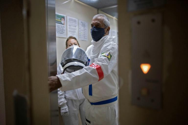 O contador Tercio Galdino e sua esposa, Alicea, pegam o elevador com trajes de proteção para sair de seu prédio em Copacabana, Rio de Janeiro, em 12 de julho de 2020